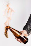 Glass bottle, the so-called Molotov cocktail in the hand of the Royalty Free Stock Photos