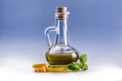 Glass bottle carafe with olive oil penne pasta and basil leaves. Royalty Free Stock Photography