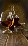 Glass and bottle with a cigar Royalty Free Stock Images