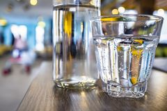 A glass and a bottle of clean drinking water stand, for quenching thirst, on a wooden table, on a bright blurred background. Close-up royalty free stock images