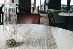 Glass bottle of coffee bean and dried flower in cafe Royalty Free Stock Photography