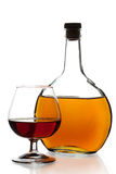 Glass and bottle of cognac Stock Images