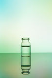 Glass bottle on a colored background Stock Images