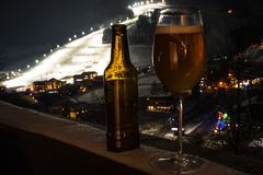 Glass and bottle with craft beer on a balcony at skiing village Royalty Free Stock Photos