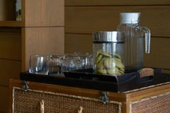 Glass bottle ,cup and cookies in jar in wooden tray for serving stock image