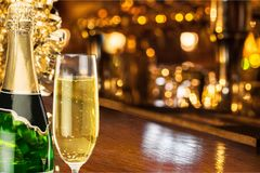 Glass and bottle of delicious champagne on blurred. Glass delicious champagne bar color pub background Stock Photos