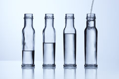 Glass bottle with different water levels Royalty Free Stock Images