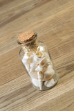 Glass Bottle filled with Seashells on Rustic Wood Stock Image