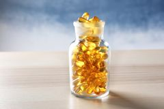 Glass bottle with fish oil capsules. On wooden table Royalty Free Stock Photo