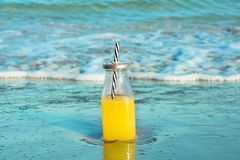 Glass bottle with fresh tropical fruits juice with straw standing on beach sand shore blue turquoise foamy sea waves. Golden sunlight. Summer vacation stock images