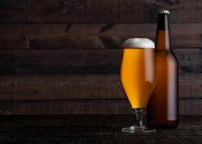Glass and bottle of golden lager beer with foam. On wooden table background Stock Photos