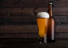 Glass and bottle of golden lager beer with foam. On wooden table background Royalty Free Stock Photography