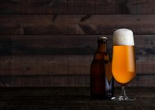 Glass and bottle of golden lager beer with foam. On wooden table background Stock Photography