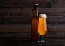 Glass and bottle of golden lager beer with foam. On wooden table background Royalty Free Stock Image