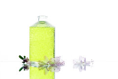 Glass bottle with green liquid and flowers Royalty Free Stock Photos