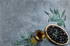 Glass bottle of homemade olive oil and olive tree branch, raw turkish black olive seeds and leaves on grey rustic table. Olives background, olivae oleum stock image