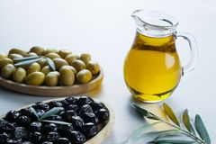 Glass bottle of homemade olive oil and olive tree branch, raw turkish green and black olive seeds and leaves on white table. Olives background, olivae oleum stock image