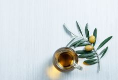 Glass bottle of homemade olive oil and olive tree branch, raw turkish green and black olive seeds and leaves on white table. Glass bottle of homemade olive oil royalty free stock photos