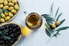 Glass bottle of homemade olive oil and olive tree branch, raw turkish green and black olive seeds and leaves on white table. Olives background, olivae oleum royalty free stock image