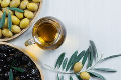 Glass bottle of homemade olive oil and olive tree branch, raw turkish green and black olive seeds and leaves on white table. Olives background, olivae oleum stock images