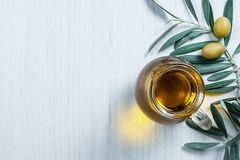 Glass bottle of homemade olive oil and olive tree branch, raw turkish green olive seeds and leaves on white table. Olives background, olivae oleum stock image