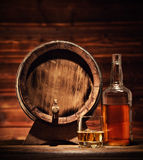 Glass, bottle and keg of whiskey with ice cubes served on wood. Glass of whiskey, bottle and keg with ice cubes served on wooden planks with keg. Vintage Stock Images