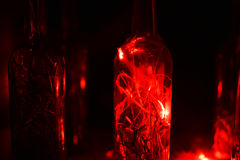Glass bottle in laser lights. Royalty Free Stock Photos