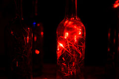 Glass bottle in laser lights. Royalty Free Stock Images