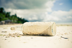 Glass bottle laying on a beach. Empty glass bottle laying on a beach, tropical island Royalty Free Stock Photography