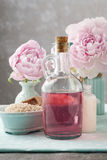 Glass bottle of liquid soap and peonies Royalty Free Stock Image