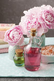 Glass bottle of liquid soap and peonies Stock Photos