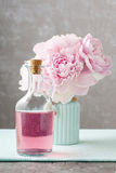 Glass bottle of liquid soap and vase with peonies Stock Photos