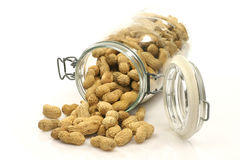 Glass bottle with lots of peanuts. In and around it Stock Image