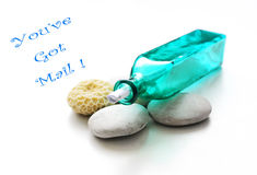 Glass bottle with mail message. You've got mail - A blue glass bottle with a message rolled up inside.  Taken with some white pebbles and coral. Concept message Royalty Free Stock Images