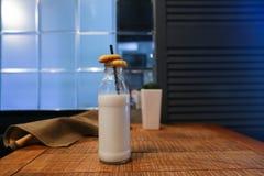 Glass bottle of milk, flower in vase and marsh drape on table ag Stock Photo
