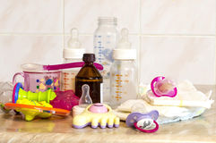 Glass bottle with the mixture for feeding, toys and baby diapers Royalty Free Stock Photos