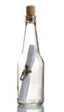 Glass bottle with note inside. Over the white Stock Images