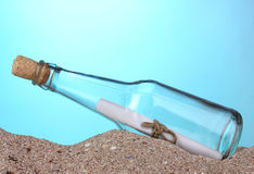 Glass bottle with note inside. On sand on blue background stock photos