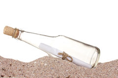 Glass bottle with note inside on sand. On white background royalty free stock photography