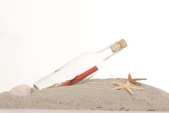 Glass bottle with note inside on sand. On white background Stock Image