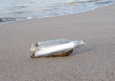 Glass bottle with note message on tropical beach Stock Image