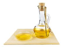 Glass bottle of oil and saucer with oil. On the mat isolated on white background Royalty Free Stock Images