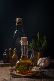 Glass bottle of olive oil with hrebs. On dark background Royalty Free Stock Photo