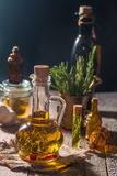 Glass bottle of olive oil with hrebs. On dark background Royalty Free Stock Image