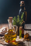 Glass bottle of olive oil with hrebs. On dark background Royalty Free Stock Images