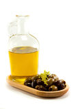 Glass bottle of olive oil and mixed olives on a wo. Glass bottle of olive oil on a wooden plate with a mixture of olives Stock Images