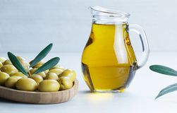 Glass bottle of olive oil and olive tree branch, raw turkish green olive seeds. And leaves on white table. green olives background, olivae oleum royalty free stock images