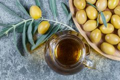 Glass bottle of olive oil and olive tree branch, raw turkish green olive seeds. And leaves on grey vintage table. green olives background, olivae oleum stock image