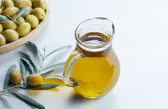 Glass bottle of olive oil and olive tree branch, raw turkish green olive seeds. And leaves on white table. green olives background, olivae oleum royalty free stock photo