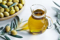 Glass bottle of olive oil and olive tree branch, raw turkish green olive seeds. And leaves on white table. green olives background, olivae oleum stock images